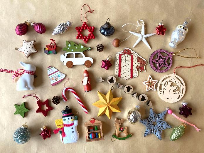 Auf dem Foto ist ganz viel Weihnachtsschmuck. Es gibt Christbaumkugeln, Sterne aus Holz und Glas und kleine Zapfen. Es gibt einen Teddy mit Geschenk und einen Nikolaus. Es gibt Zuckerstangen, eine Eule aus Glas und einen Osterhasen. Es gibt ein Auto mit Tannenbaum auf dem Dach. Es gibt einen Schneemann und eine Glocke.